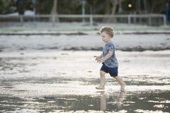 Ung pojke som spelar i grunt vatten Arkivbilder