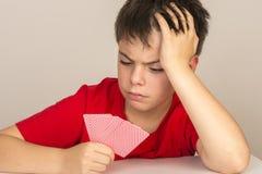 Ung pojke som spelar kort Arkivbild