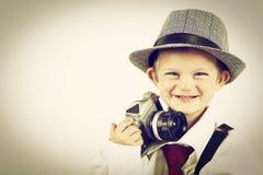 Ung pojke som spelar med en gammal kamera för att vara fotograf Royaltyfria Bilder