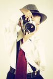 Ung pojke som spelar med en gammal kamera för att vara fotograf Royaltyfri Foto