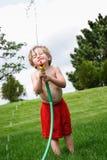 Ung pojke som spelar med en slang royaltyfri foto