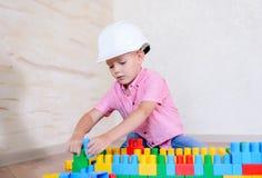 Ung pojke som spelar med färgrika byggnadskvarter Arkivbilder