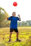 Ung pojke som spelar med fotbollbollen utomhus. Arkivbilder