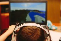 Ung pojke som spelar på datoren Arkivbild