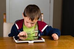 Ung pojke som spelar på minnestavladatoren Royaltyfria Bilder