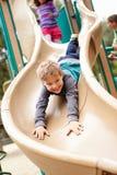 Ung pojke som spelar på glidbana i lekplats Royaltyfria Bilder