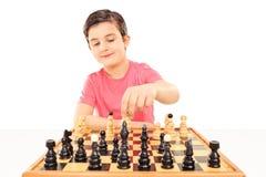 Ung pojke som spelar schack som placeras på en tabell arkivbilder
