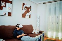 Ung pojke som spelar videospel med exponeringsglas 3d arkivbilder