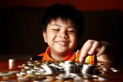 Ung pojke som staplar eller traver mynt royaltyfri fotografi