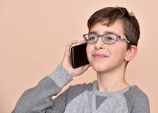 Ung pojke som talar på hans smarta telefon Arkivfoton