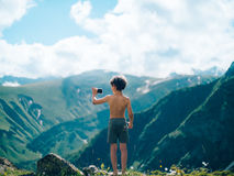 Ung pojke som tar fotoet med smartphonen i berg Royaltyfria Bilder