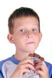 Ung pojke som äter stången av choklad Arkivfoto