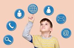 Ung pojke som trycker på jordklotknappen på en faktisk pekskärm royaltyfria bilder