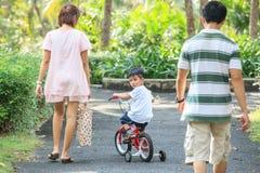 Ung pojke som tycker om rida cykeln med familjen i trädgården arkivfoto