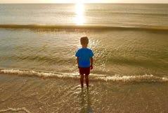 Ung pojke som ut ser till en guld- solnedgång som reflekterar i havet Royaltyfria Foton