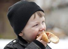 Ung pojke som äter hotdogen Royaltyfria Foton