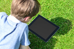 Ung pojke som utomhus använder den digitala minnestavlan Arkivbilder