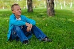 Ung pojke som utomhus sitter Arkivbilder