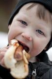 Ung pojke som äter hotdogen Arkivbilder