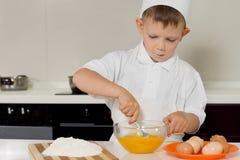Ung pojke som viftar ägg med en gaffel Royaltyfri Fotografi