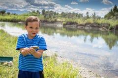 Ung pojke som visar fisken som han fångade arkivbilder