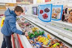 Ung pojke som väljer glass på shopping i supermarket Royaltyfri Bild
