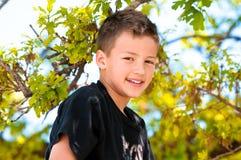 Ung pojke upp i trädet Fotografering för Bildbyråer