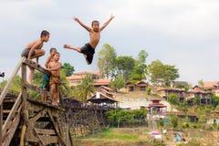 Ung pojkebanhoppning in i sjön på träbron Arkivbild