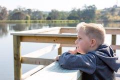 Ung pojkebenägenhet på en brygga som förbiser en sjö som ser ledsen arkivfoto