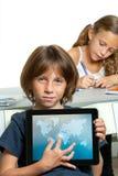 Ung pojkedeltagare som visar världsöversikten på tableten. Arkivbild