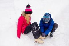 Ung pojkehjälp till flickabandkängsnörena åker skridskor upp Fotografering för Bildbyråer