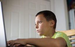 Ung pojkeplayin på datoren arkivbild