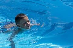 Ung pojkeswimmimng i pölen för första gång arkivfoton