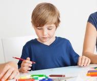 Ung pojketeckning med färgrika blyertspennor Arkivfoton