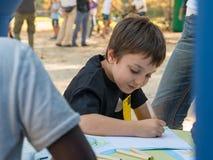 Ung pojketeckning på ett papper med den kulöra blyertspennan i en parkera Royaltyfria Bilder