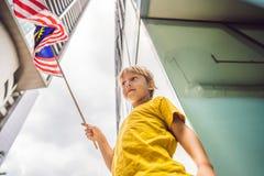 Ung pojketurist med flaggan av Malaysia nära skyskraporna Resa med ungebegrepp royaltyfri foto