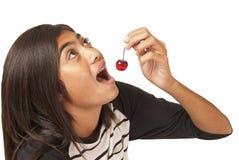 Ung Polynesian flicka som äter en körsbär Arkivfoto