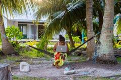 Ung Polynesian kvinna i en hängmatta med ett anteckningsbokarbete utomhus under palmträd Tuvalu Polynesien, South Pacific hav royaltyfri bild