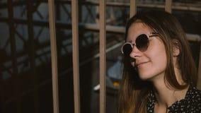 Ung positiv kvinnlig europeisk turist i stilfullt le för solglasögon som ser tycka om upp sikten på den Brooklyn bron 4K stock video