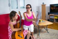 Ung preteenflicka som har gitarrkurs hemma Arkivfoton