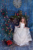 Ung prinsessa i en vit klänning med en tiara på hennes huvud på julgranen Royaltyfria Foton