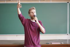 Ung professorlärare som talar med mikrofonen i hörsalen som står den near svart tavla Arkivfoton