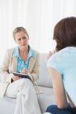 Ung psykolog som lyssnar uppmärksamt till hennes patient arkivfoto