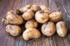 Ung rå okokt potatis på tabellen arkivfoto