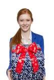 Ung röd haired flicka som framlägger en gåva Royaltyfri Foto