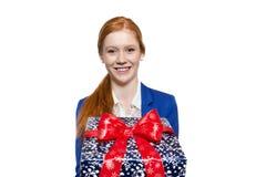 Ung röd haired flicka som framlägger en gåva Fotografering för Bildbyråer