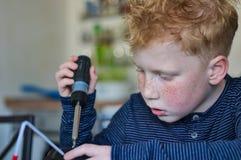 Ung röd haired pojke, genom att arbeta royaltyfria foton