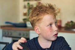 Ung röd haired pojke, genom att arbeta arkivbild