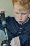 Ung röd haired pojke, genom att arbeta arkivfoto