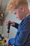 Ung röd haired pojke, genom att arbeta arkivfoton